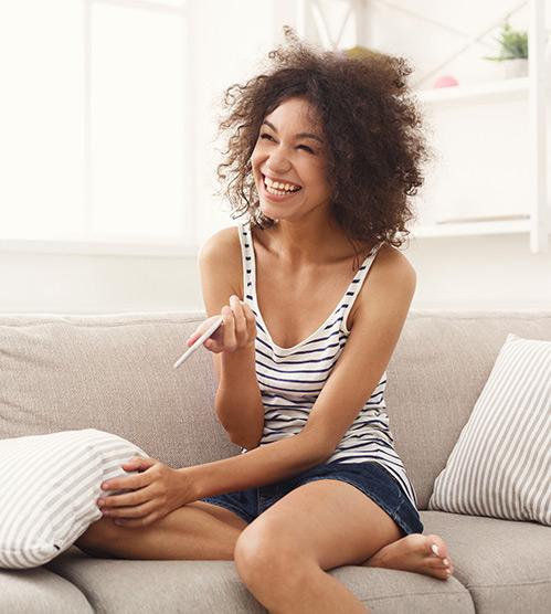 Femme souriant après avoir découvert le résultat de son test de grossesse